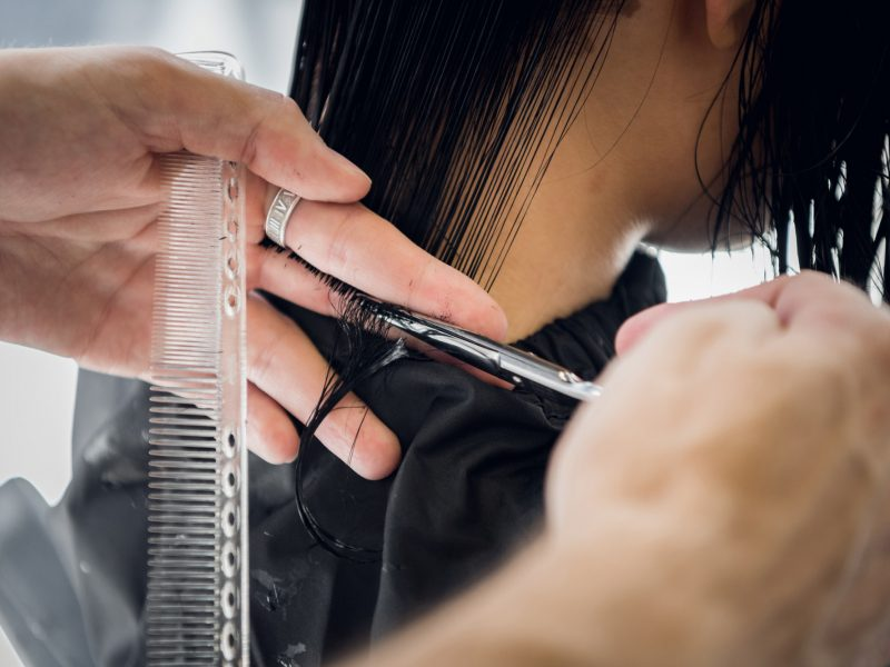 Hairdresser cutting client's hair in salon with scissors closeup. Using a comb
